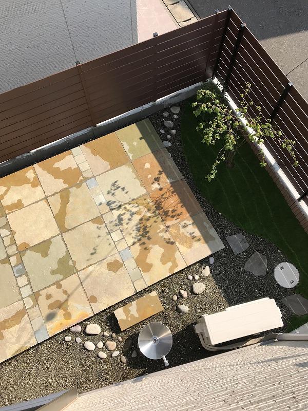 禅ガーデンをテーマに石のテラスを配置。苔を用いた築山を毛足の短い苔風の人工芝で現代風に表現。その周りを枯山水風アレンジで囲う。