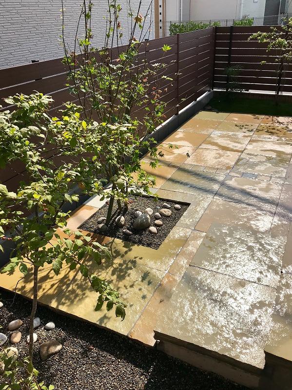 天然石の浮きテラスと浮き階段。テラスの中には四角く切り取ったなかにコハウチワカエデと枯山水テイストの箱庭。浮きテラスを囲うように、同じく枯山水テイストのエリアとナツハゼを配置。